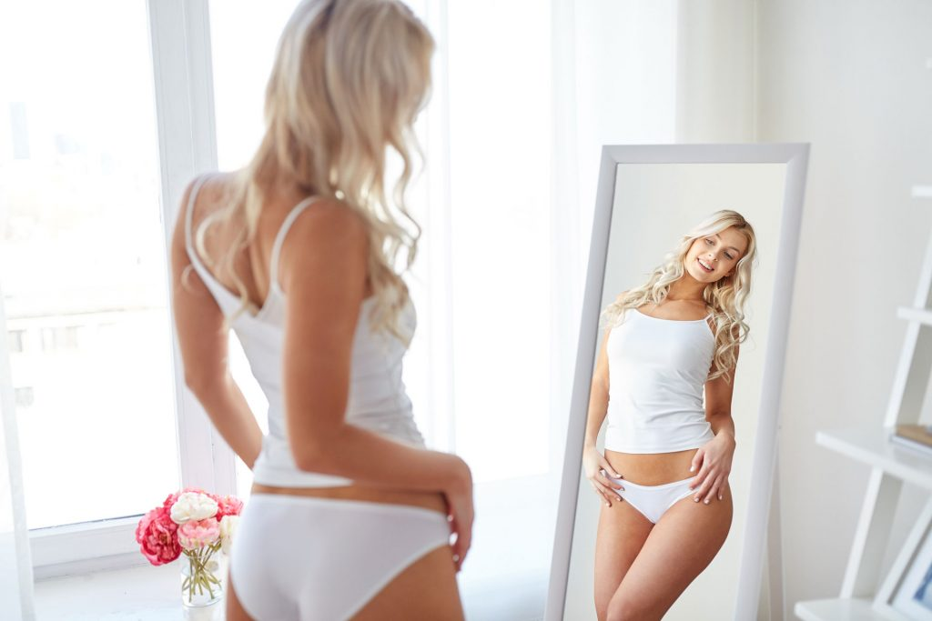 Woman with beautiful shape checking on the mirror